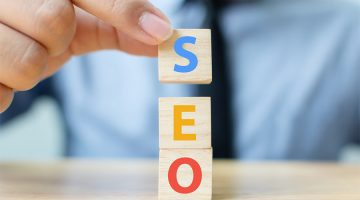 Search engine optimization concept. Hand putting wood block cube shape with word SEO