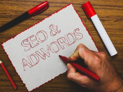 Word writing text Seo and Adwords. Business concept for Pay per click Digital marketing Google Adsense Man hand holding marker notebook paper expressing ideas wooden background.